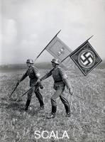 ******** First visit of Benito Mussolini in Germany. The flags of Mussolini and Adolf Hitler are carried by two soldiers to the 'Feldherrenhuegel' during a military maneuver. Photography. 1938
